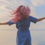 Frau am Meer Blick auf Horizont Arme ggeöffnet, wehendes Haar