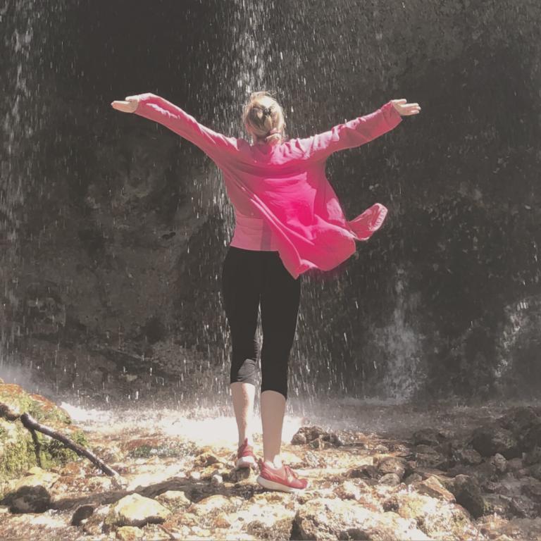 Frau in pinker Bluse vor Wasserfall, Hände nach oben ausgestreckt