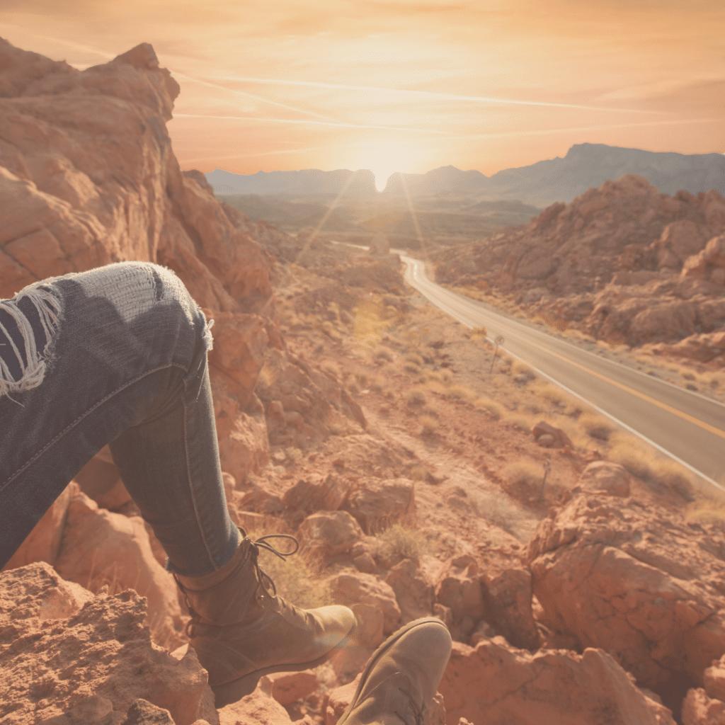 Beine & Schuhe einer sitzenden Frau auf Berg mit Blick auf Outback-Straße mit Bergen und Sonne am Horizont